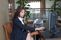 Side profile of a businesswoman sitting at a table and working on a computer