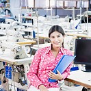 Portrait of a female fashion designer holding a file in a textile industry and smiling