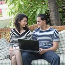 Young couple sitting with a laptop on a couch and looking at each other