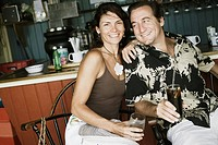 Close-up of a mid adult couple holding glasses of drink in a restaurant