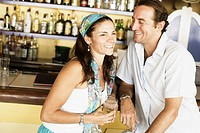Mid adult couple sitting at a bar counter and smiling