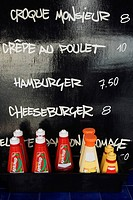 Close-up of tomato ketchup bottles in front of menu list on a blackboard