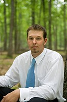 Portrait of young businessman sitting in forest
