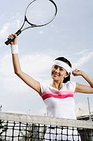 Young woman holding tennis racket with arms raised, smiling, portrait