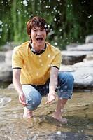 Young man splashing water, smiling, portrait