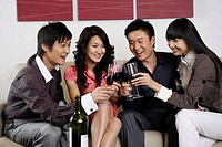 Young toasting wineglasses, smiling