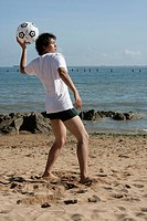 Young man with soccer ball at beach