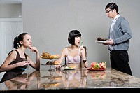 Man serving women at breakfast table