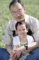 Girl sitting with grandfather on field