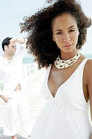 Portrait of young woman at beach with man in background