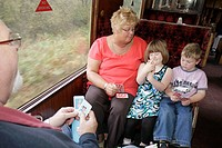UK, England, North Yorkshire, Goathland, North Yorkshire Moors Railway, passengers, family, playing cards, grandparents, girl, boy, siblings,