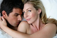 Young man kissing woman´s shoulder in bed