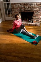 Portrait of a young woman in sports clothing exercising on mat by fire place