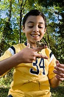 Boy holding a frog on his fingers at forest