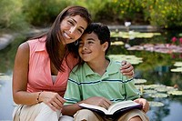 Young woman sitting with her son by pond reading book