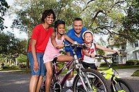 Portrait of a family standing with bicycle on the road