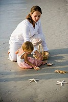 Girl with mother playing on the beach