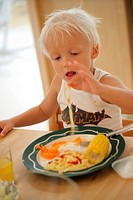 A boy eating food at the table