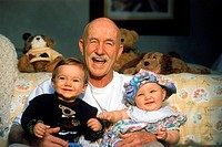Close_up of happy grandfather with two grandchildren