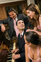 Young man playing a piano and looking at a young woman