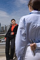Businesswoman holding scissors behind back and talking to colleague