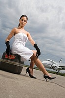Portrait of a young woman sitting on her luggage