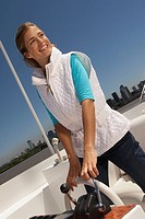 Young happy woman steering boat