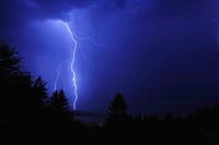 Lightning bolts streak across the sky and strike on the shores of Shuswap Lake during a summer storm in Salmon Arm, British Columbia, Canada