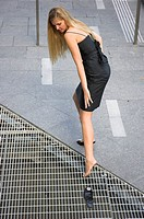 Young woman looses her high heeled shoe in a pavement drain cover