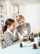 Woman helping teenage girl to make christmas ornaments