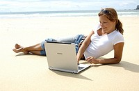 Close_up of woman using laptop on the beach