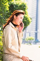 Image of a Young Adult Woman Talking on her Cell Phone Outside, Side View, Differential Focus