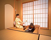 Woman in kimono holding a bamboo dipper in a tea room, side view, Japan