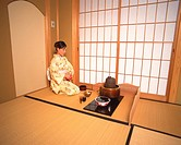 Woman in kimono sitting in a tea room, side view, Japan