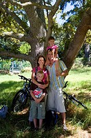Family of four with bicycles beneath tree, smiling, portrait