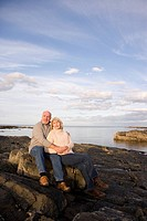 Senior couple on rocks by sea, man embracing woman, smiling, low angle view