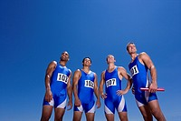 Male athletes in row, smiling, low angle view