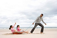 Father pulling daughters 5-9 on sledge on beach, side view