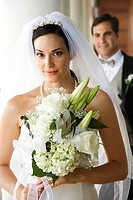 Caucasian mid_adult bride holding bouquet with groom in background.