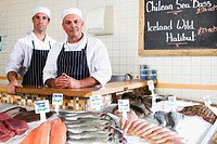 Fishmongers behind counter in shop, smiling, portrait