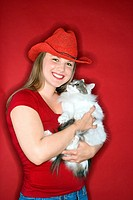 Young Caucasian female adult holding cat wearing cowboy hat.