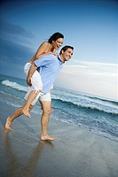 Caucasian mid_adult male carrying female piggyback style on beach.