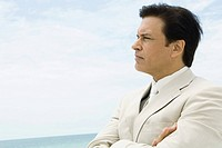 Businessman crossing arms, looking at distance, sea in background