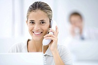 Young woman in office, using landline phone