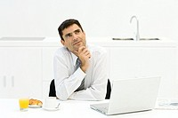 Businessman sitting at table with laptop computer and breakfast, hand under chin, looking up