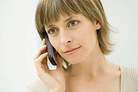 Woman using cell phone, looking away, close-up
