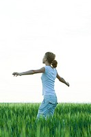 Teenage girl standing in field with arms outstretched, side view