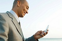 Businessman looking down at cell phone outdoors, side view, low angle