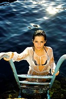 A beautiful young woman posing on a ladder by the water in Malta