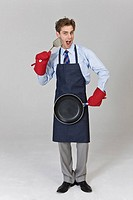 Man holding frying pan and turner